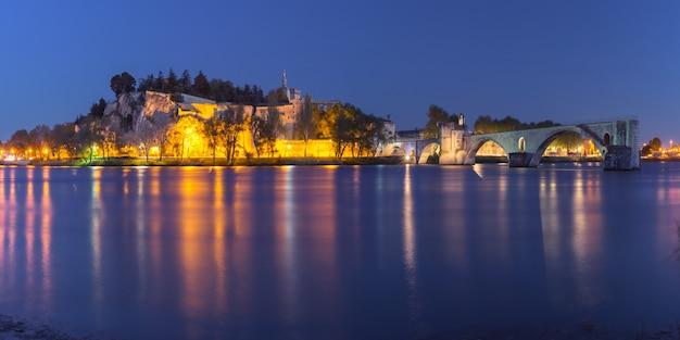 Panoramablick auf die berühmte mittelalterliche brücke saint benezet und den palast der päpste während der blauen abendstunde, avignon, südfrankreich