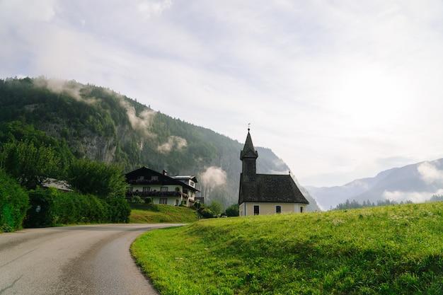 Panoramablick auf die idyllische kirche am morgen in den alpen. schöne neblige morgenlandschaft im alpenraum, österreich. toller morgenblick auf neblige berge, nebel, haus und grüne wiese in österreich.