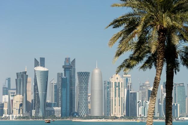 Panoramablick auf die moderne skyline von doha durch verschwommene palmen. katar am sonnigen tag.