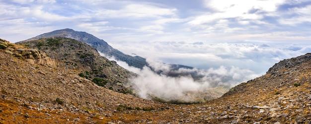 Panoramablick auf die sierra de guadarrama mit ihren wolken von der spitze eines berggipfels.