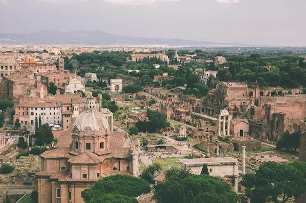Panoramablick auf die stadt rom mit forum romanum und kolosseum von vittorio emanuele ii monument auch bekannt als vittoriano. sonniger sommertag und dramatischer blauer himmel