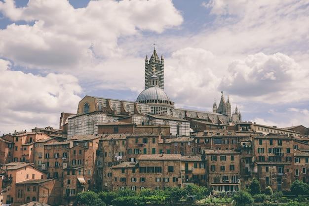Panoramablick auf die stadt siena mit historischen gebäuden und dem weit entfernten dom von siena (duomo di siena). sonniger sommertag und dramatischer blauer himmel
