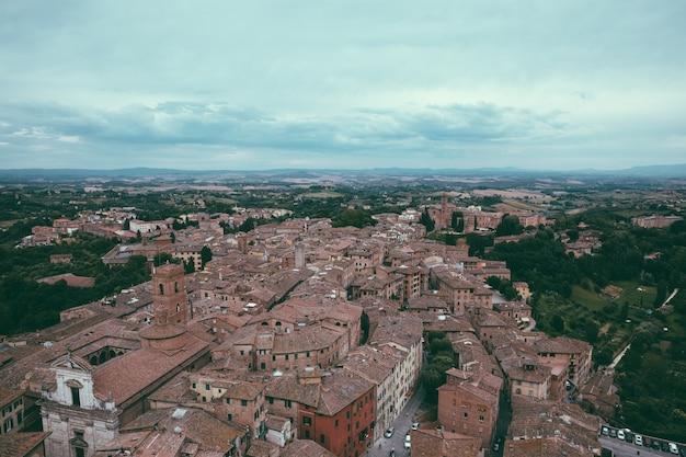 Panoramablick auf die stadt siena mit historischen gebäuden und weit entfernten grünen feldern von torre del mangia ist ein turm in der stadt. sonniger sommertag und dramatischer blauer himmel