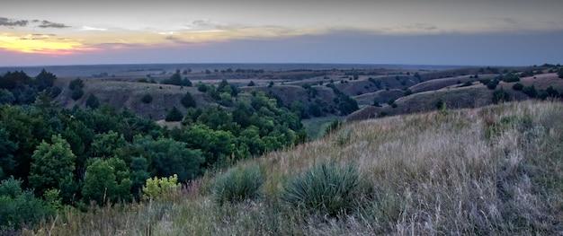 Panoramablick auf eine schöne landschaft mit gebirgszügen unter dem sonnenuntergangshimmel