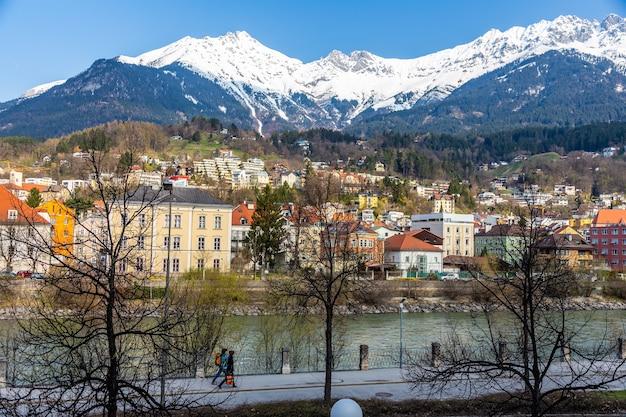 Panoramablick auf farbenfrohe gebäude und berge gegenüber dem fließenden fluss von innsbruck österreich