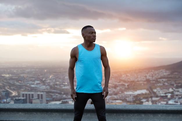 Panoramablick auf freien schwarzen muskulösen mann in aktivkleidung, hat übungen im freien, posiert über wunderschöner landschaft, sonnenaufgang im morgengrauen, stadtgebäude, klarer himmel, genießt freiheit, frische luft und einsamkeit