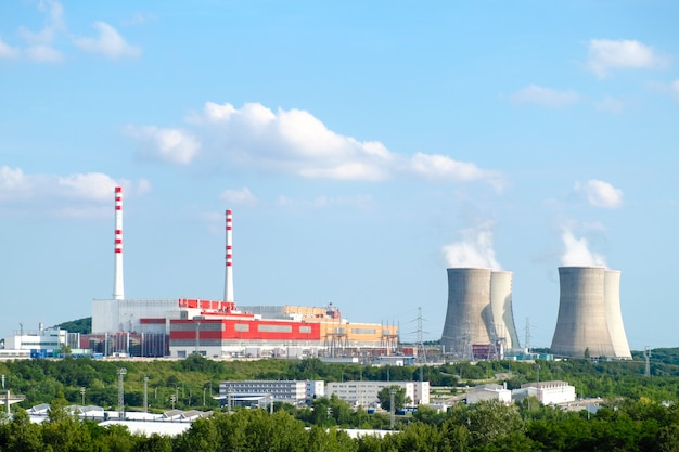 Panoramablick auf kernkraftwerk mit dampfenden kühltürmen auf blauem himmel
