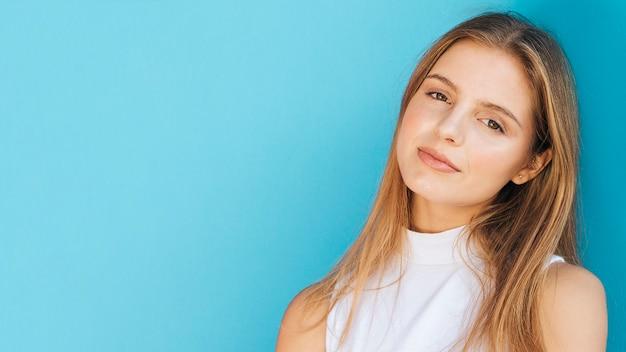 Panoramablick der blonden jungen frau gegen blauen hintergrund
