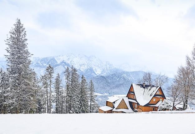 Panoramablick des alten traditionellen bauernhauses, das auf einem hügel in den szenischen winterwunderland-landschaftswolken während der wintersaison sitzt