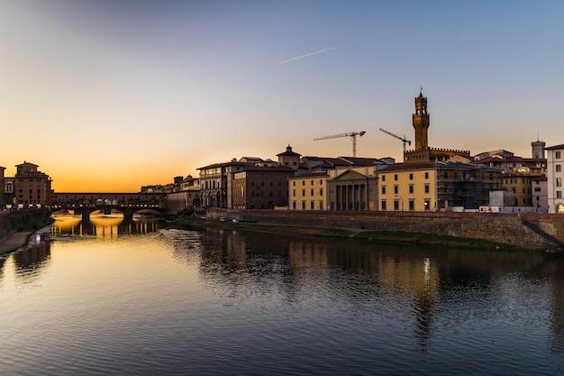 Panoramablick des berühmten ponte vecchio mit fluss arno bei sonnenuntergang in florenz, italien