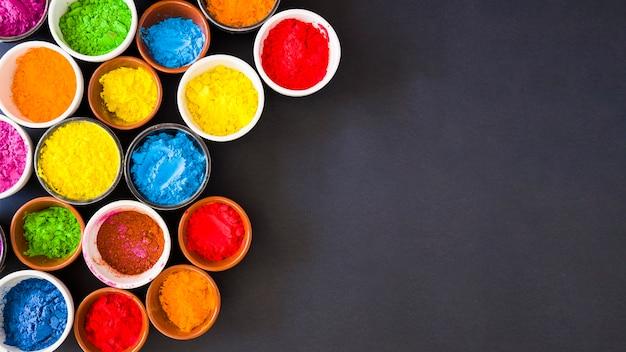 Panoramablick des holi farbpulvers in den schüsseln auf schwarzem hintergrund