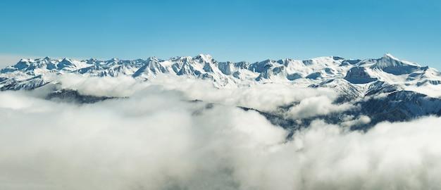 Panoramablick des schneebedeckten wintergebirges in den wolken in abchasien am blauen himmelhintergrund