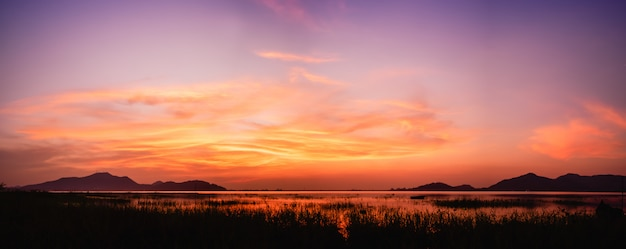 Panoramablick des sonnenuntergangs über dem see mit dämmerungshimmel