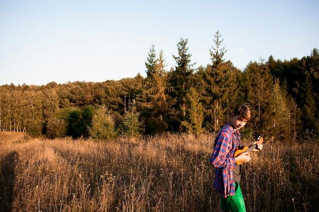 Panoramablick des waldes und des mannes, die ukulele spielen
