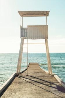 Panoramablick des weißen hölzernen rettungsschwimmerturms am hintergrund im vintage retro-stil