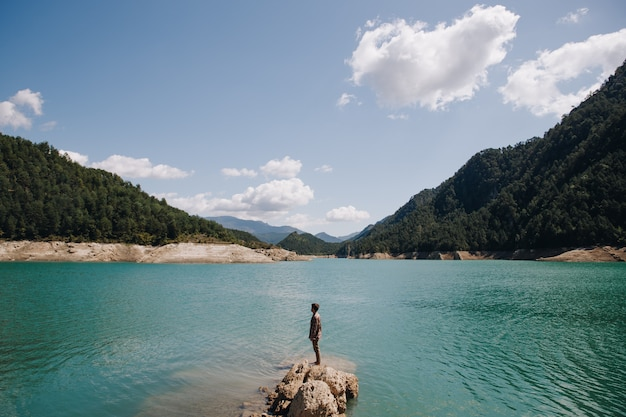 Panoramablick eines mannes, der auf einem felsen in einem ruhigen see des blauen wassers umgeben durch berge an einem sonnigen tag im sommer steht