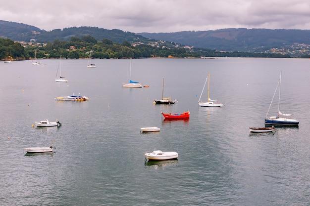 Panoramablick mit seemannsbooten in der nähe eines kleinen dorfes im norden spaniens