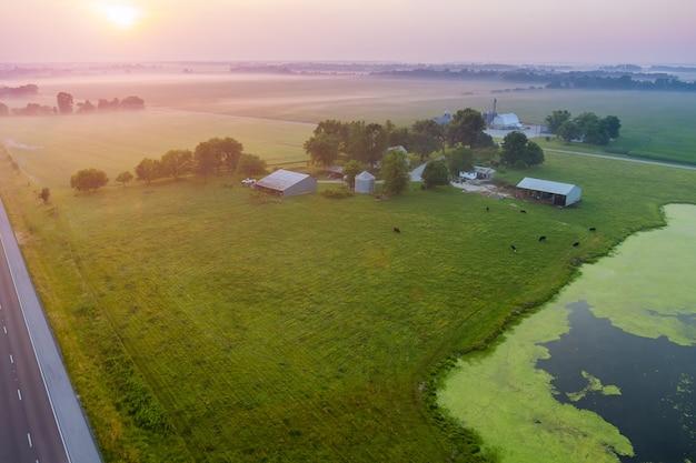 Panoramablick mit sonnenaufgang auf einem feld mit grünem gras in der nähe eines teiches in einem kleinen dorf