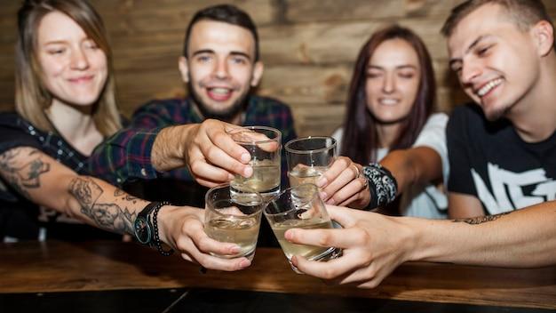 Panoramablick von den freunden, die alkoholgetränkgläser rösten