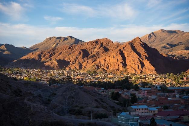 Panoramablick von tupiza-dorf mit glühendem rotem gebirgszug bei sonnenuntergang. von hier aus starten sie den herausragenden 4-tägigen roadtrip nach uyuni salt flat, einem der wichtigsten reiseziele in bolivien.