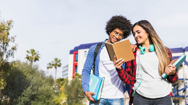 Panoramablick von verschiedenen jugendpaaren, die das buch außerhalb des campus lesen