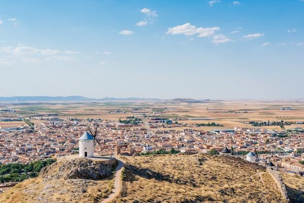 Panoramafoto der windmühlen von consuegra mit einem dorf im hintergrund in toledo, spanien.