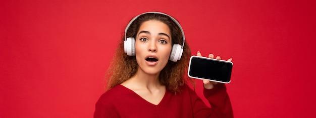 Panoramafoto einer attraktiven, überraschten jungen, brünetten, lockigen frau, die einen dunkelroten pullover trägt, isoliert