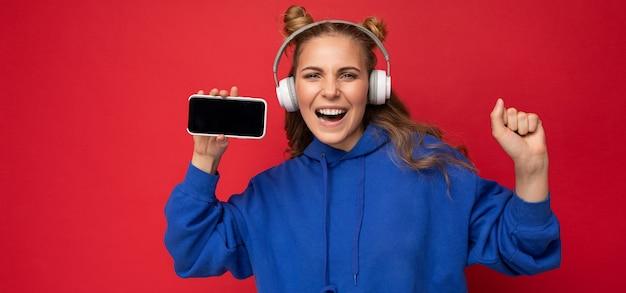 Panoramafoto einer faszinierenden, glücklich lächelnden jungen frau, die einen stylischen blauen hoodie trägt, isoliert über