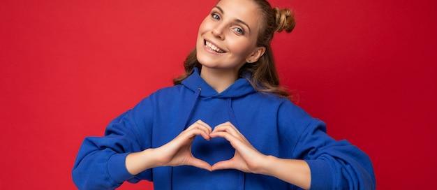 Panoramafoto einer jungen, glücklich lächelnden, positiven, attraktiven blonden frau mit aufrichtigen emotionen, die einen stilvollen hellblauen hoodie trägt, der auf rotem hintergrund mit kopienraum isoliert ist und herzgeste zeigt