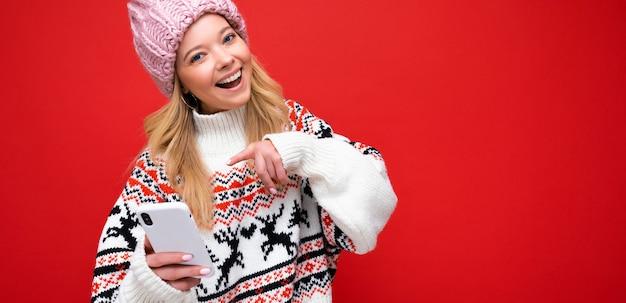 Panoramafoto einer schönen lächelnden jungen blonden frau mit warmer strickmütze und winter warm