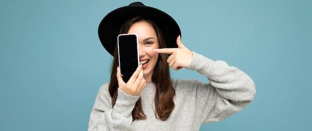 Panoramafoto einer schönen positiven frau mit schwarzem hut und grauem pullover mit mobiltelefon