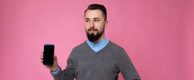 Panoramafoto eines hübschen, glücklichen, kühlen jungen, unrasierten, brünetten mannes mit stylischem grau mit bart