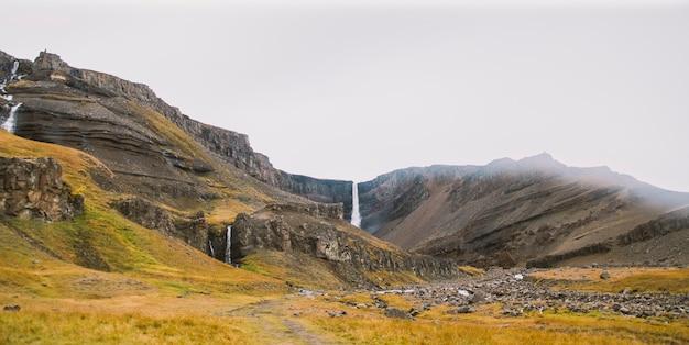 Panoramafotos berühmter isländischer wasserfälle an bewölkten tagen mit geologischen formationen.