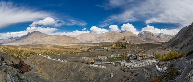 Panoramalandschaftsansicht in herbst- und maitreya buddha-statue mit himalaja-bergen