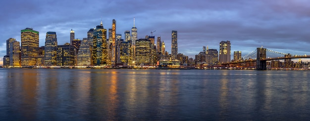 Panoramaszene von new york cityscape mit brooklyn-brücke neben dem east river