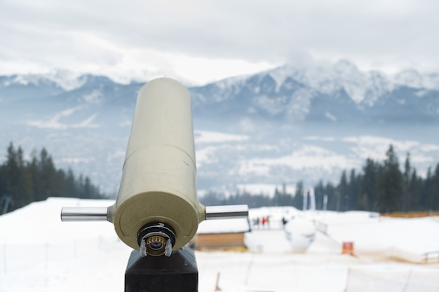 Panoramateleskop mit bergblick im winter