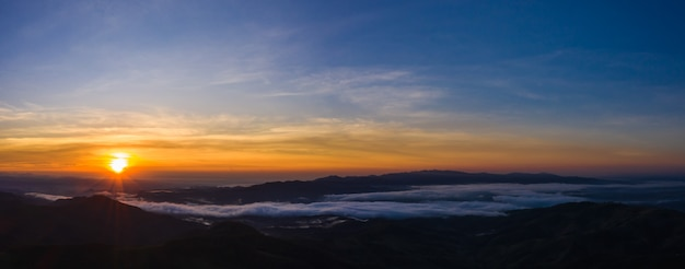 Panoramische landschaft das sonnenlicht mit blauem himmel auf dem berg am morgennebel