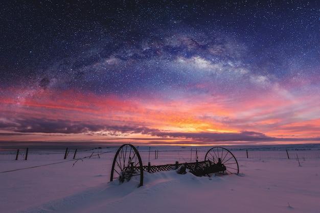 Panoramische winterlandschaft im sonnenaufgang mit landschaft des nächtlichen himmels der doppelbelichtung