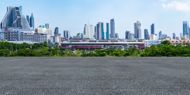 Panoramischer leerer konkreter boden und grünes gras im schönen park unter dem blauen himmel