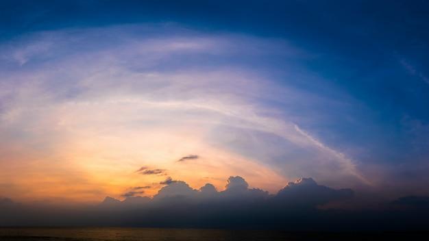 Panoramischer sonnenuntergang mit flaumiger wolke in der dämmerung