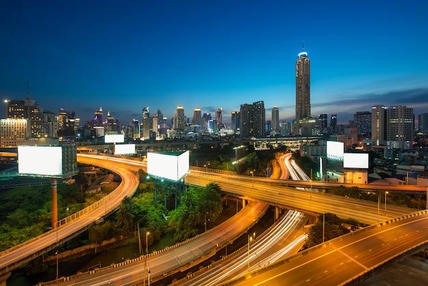 Panoramisches bangkok-stadtgebäude mit schnellstraße herein in die stadt in der dämmerung in bangkok, thailand.