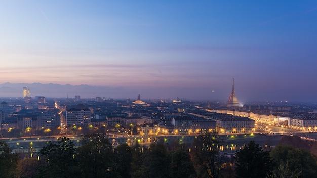Panoramisches stadtbild von turin (turin) von oben genanntem an der dämmerung