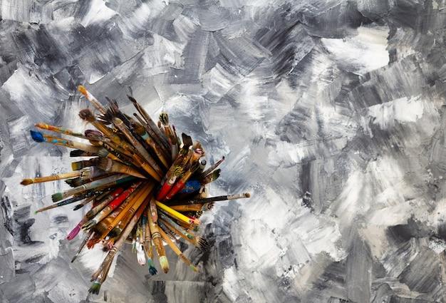 Pantbrush oder bürsten im korbhalter bei gemalter hintergrundtextur und farben auf abstrakter tischoberfläche, kunstmalerkonzept
