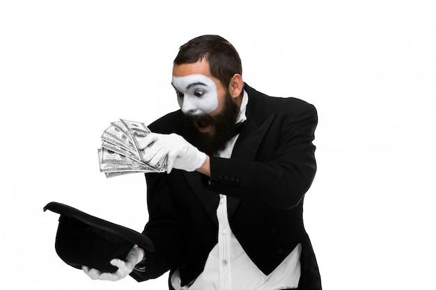 Pantomime als geschäftsmann, der dollar in hut legt