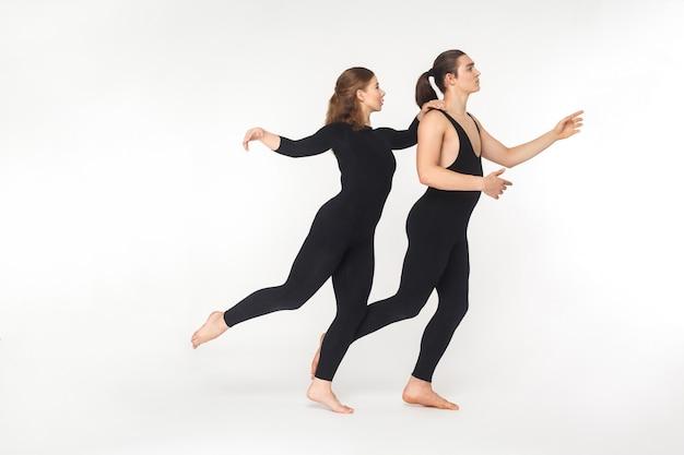 Pantomime-konzept. zwei künstler stehen auf zehe und balancieren. studioaufnahme, isoliert auf weißem hintergrund