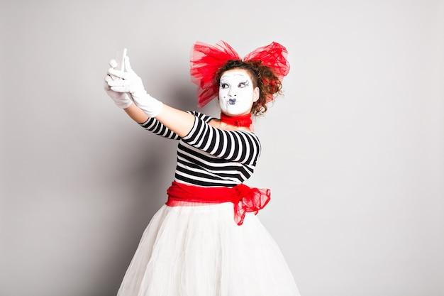 Pantomime macht ein selfie-foto. frau mit smartphone. konzept des aprilscherzes.