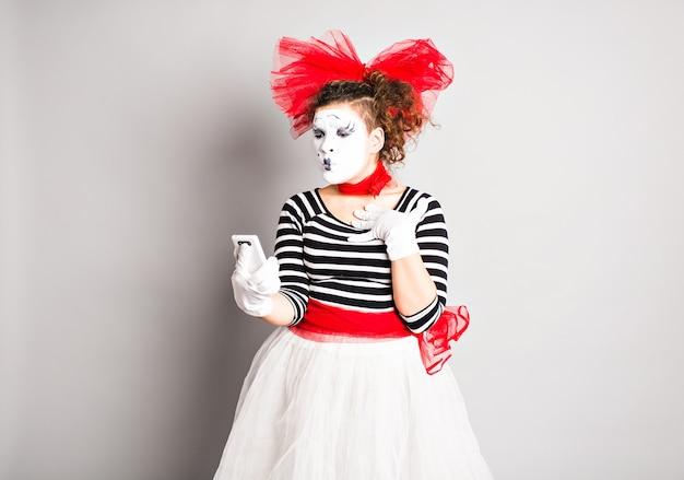 Pantomime mit smartphone. konzept des aprilscherzes.