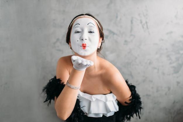 Pantomime-theaterschauspielerin mit weißer make-up-maske, die im studio aufwirft. c.
