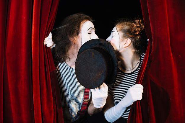 Pantomimekünstler zwei, der hinter dem vorhangküssen steht