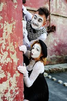 Pantomimen, die sich hinter einer mauer verstecken